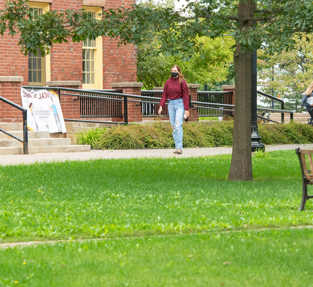a student walking in front of upei's main building
