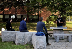 Three students sit on stone slabs in an outdoor setting as they listen to a fourth student instructing them