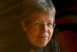 A photo portrait of a woman with shorter hair and glasses
